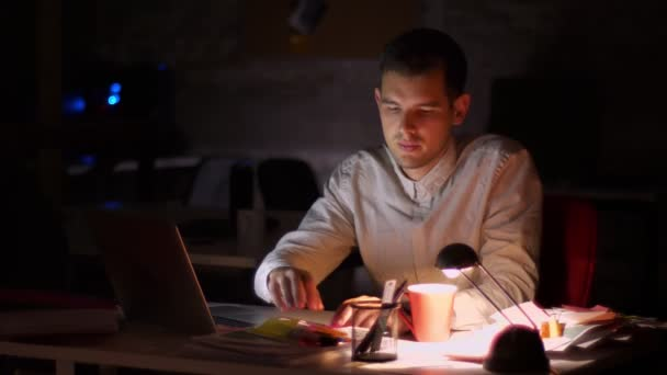Footage of focused working male sitting and checking documents while holding papers and looking at screen of laptop , spending time with productivity, black background, late