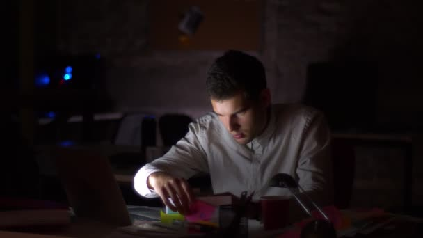 Shooting of dark office, light from screen ar shining on his face while he is sitting looking at computer and checking papers, holding them with focused confident face, indoor illustration