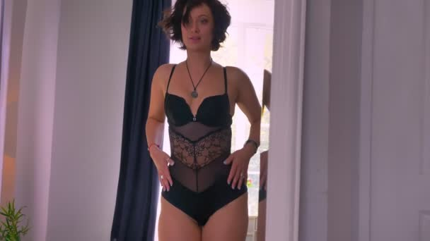 Shooting of caucasian sexy women with wavy black hair and lace underwear corrects her outfit and flaunts in front of the mirror, relaxing
