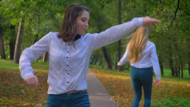 Two Funny Caucasian Girls Are Hanging Out Together, Jumping In Beautiful Green Park, Throwing Leaving, Dancing and Enjoying Life, Happy Moments