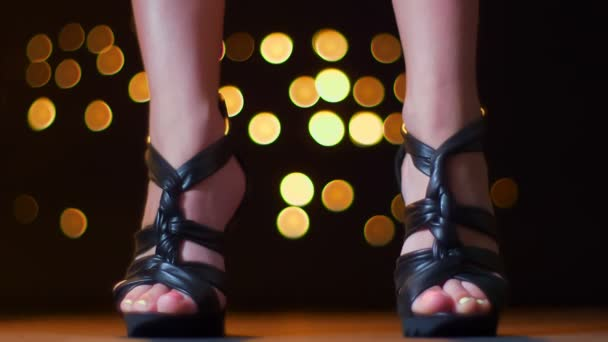 Amazing footage legs of woman close-up standing near camera wearing high heels on black shoes, bright light background indoors