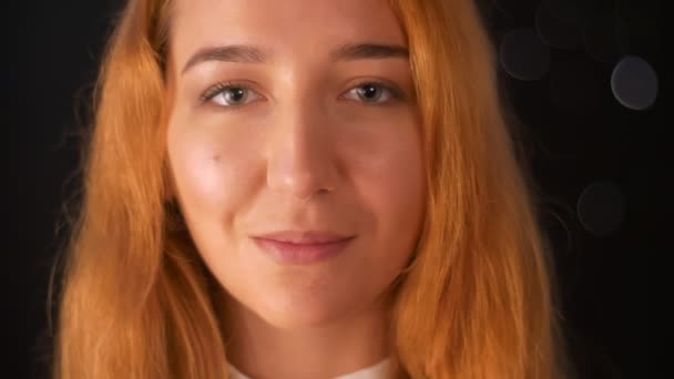 Nádherná žena Kavkazský zázvor stojí zblízka a při pohledu přímo kamera s pěkně s úsměvem tempo a otevřít přirozený vzhled na tmavém pozadí