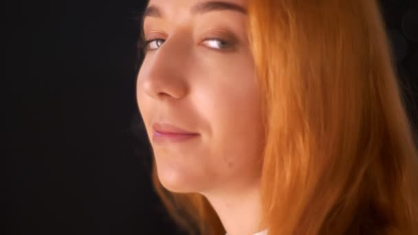Uvolněný Kavkazský zázvor ženské stojící detail v profilu a odvrátila hlavu při pohledu na fotoaparát zelené oči, tmavé pozadí a chlazení vibrace