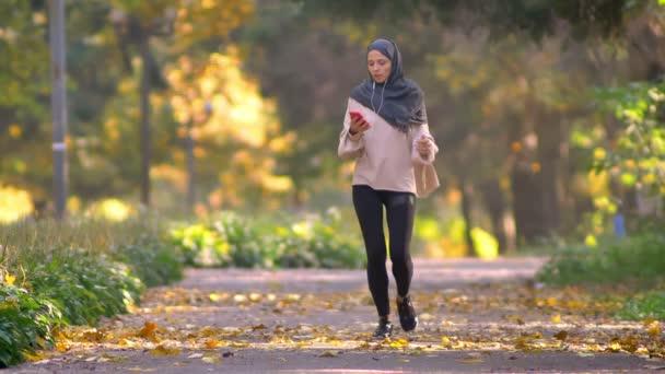 Muslimské ženy v hidžábu jde zaběhat v podzimní park, zastaví se podívat do smartphone a pokračuje systémem