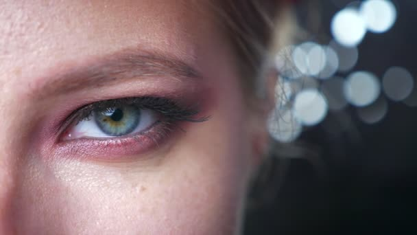 Closeup beautiful green eye of caucasian female looking straight with awesome makeup on dark background isolated