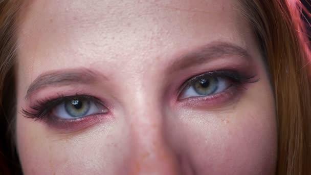 Čisté krásné zelené oči v eyeshadows zblízka při pohledu na fotoaparát, Kavkazský žena stojící na černém pozadí, prokazující barevné kosmetické