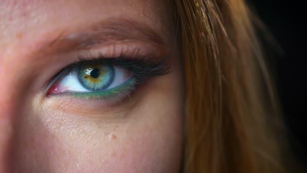 Nahaufnahme graues Auge einer kaukasischen Frau, die mit ruhigem Gesicht und fokussiertem Blick in die Kamera blickt, im Innenraum hinter dem Hintergrund stehend, Kosmetikvibes und kühle Stimmung