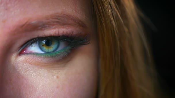Amazing close up eye of caucasian blonde woman in green glowing eyeshadows and perfect cosmetics, looking at camera relaxed and not blinking, in dark studio, fashion illustration