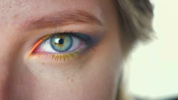 Closeup krásné oko s barevné duhové kosmetiky a stíny, díval se přímo na kameru a blikající chlad, módní make-up ilustrace