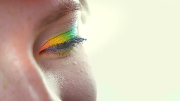 Detailní záběr oka v rainbow eyeshadows při pohledu na fotoaparát, zelené, žluté a modré, bílé pozadí, čistou tvář v kosmetice