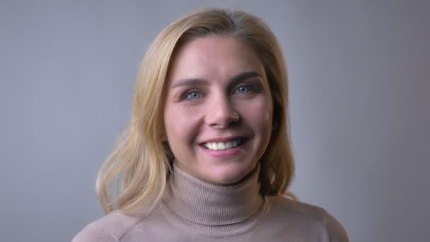 Detailní portrét středního věku blond žena sledoval a usmíval se spokojeně do kamery na šedém pozadí.