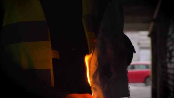Man in yellow vest sets fire to a Molotov cocktail in a dark alley. Front view, riot, revolution concept