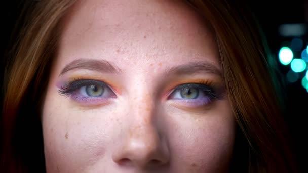 Detailní portrét atraktivní blondýna ženské úsměv do kamery s barevné oční make-up na pozadí modrá světla