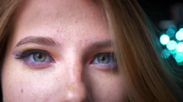 Szőke nő, spinning, és mosolyogva, kamera, színes szem make-up, a háttér kék fények közeli portréja.