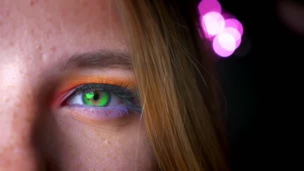 Detail napůl portrét blond žena se zelenýma očima, světlé a barevné make-up na pozadí růžového světla