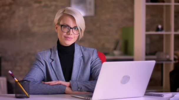 Portrait of blonde short-haired businesswoman in glasses smiling positively into camera in office.