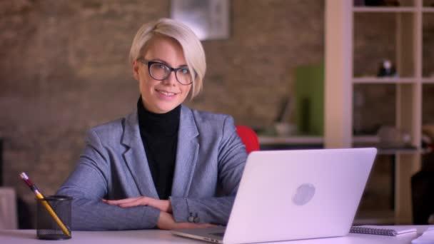 Portrét blond krátké vlasy podnikatelka v brýlích a ruce zkřížené na tabulce úsměv do kamery v úřadu.