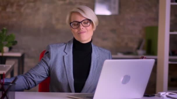 Portrét středního věku krátké vlasy podnikatelka v brýlích aktivně tanec na židli v kanceláři.