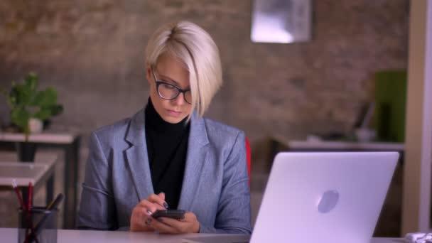 Porträt einer kurzhaarigen Geschäftsfrau mittleren Alters mit Brille, die mit Smartphone arbeitet, lächelt im Büro in die Kamera.