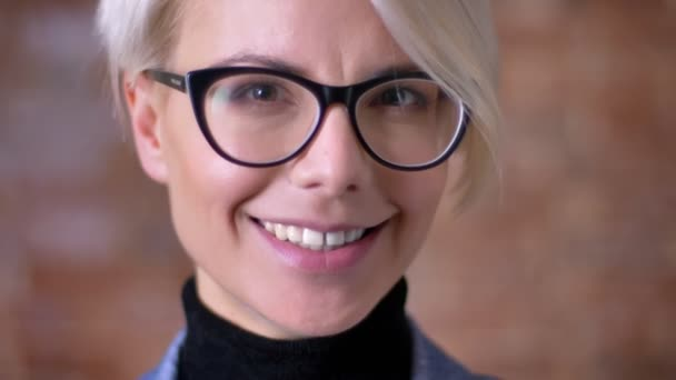Close-up portrait of blonde short-haired woman in glasses smiling gladly into camera on bricken wall background.