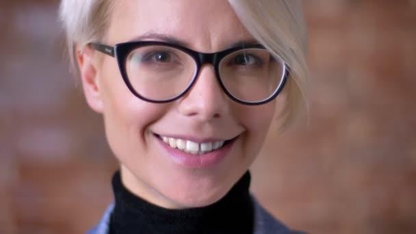 Detail portrét blond krátké vlasy žena v brýlích usmívat radostí do kamery na zeď bricken na pozadí