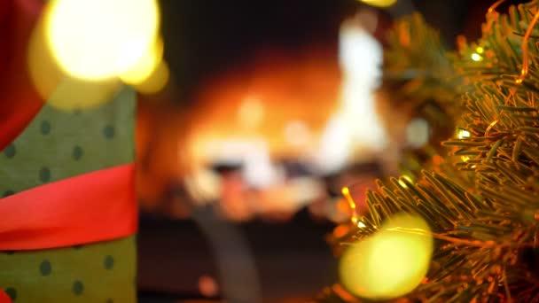 Dát dárek na stůl. Vánoční tři na bokeh krb záře světla pozadí.