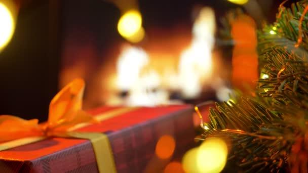 Vánoční červená dárková krabička. Vánoční tři na bokeh krb záře světla pozadí