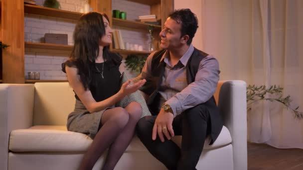 Portrét arabské pár příjemně rozhovory s ostatními sedí na pohovce v obývacím pokoji.