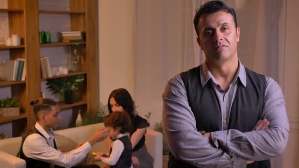 Podobizna arabské muže vážně dívat do kamery stál s rukama překročili v obývacím pokoji s rodinou na pozadí.