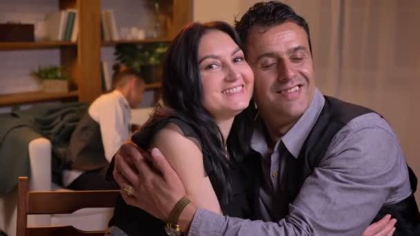 Arab portréja házastársak egymást átölelve, és mosolyogva a kamerába ül a nappaliban kanapé.