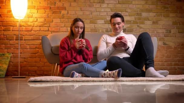 Nahaufnahme Porträt zweier junger kaukasischer Freunde, die auf Teppich sitzen und leckere Heißgetränke in gemütlicher Atmosphäre zu Hause trinken.
