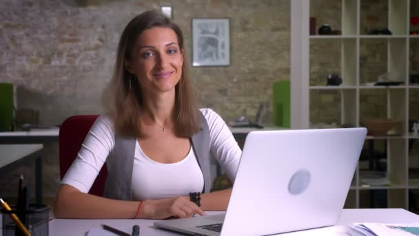 Attractive office worker sitting in fron of the laptop looking on a camera and smiling being happy on the workplace