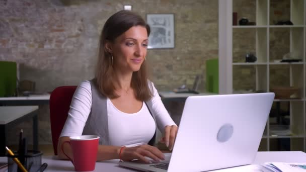 Attractive female office worker typing on the laptop drinking coffee gets statisfied and smiles being on thec workplace indoors
