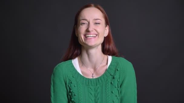 Detailní záběr na atraktivní šťastný Kavkazský žena s rudými vlasy směje a je překvapen, kartáčuju rukou