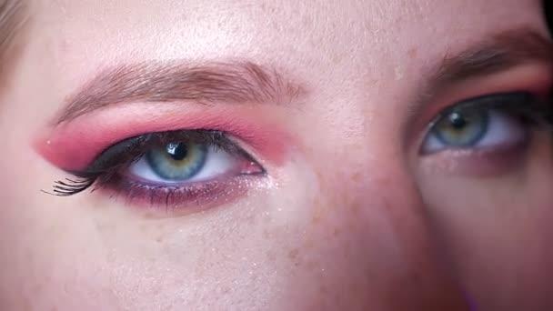 Detailní záběr na atraktivní ženské modré oči make-up s odstíny růžové a okouzlující úrovní očí při pohledu přímo na kameru