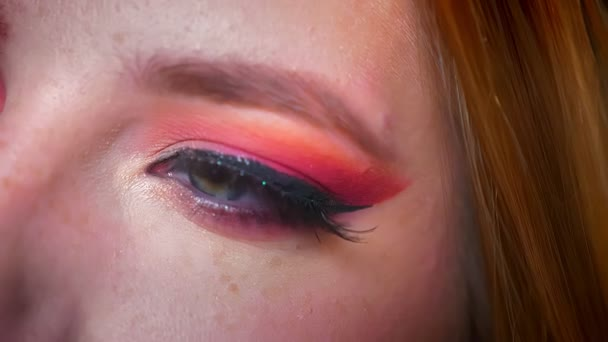 Detailní záběr na atraktivní ženské modré oči make-up s odstíny růžové a okouzlující třpytí. Pravé oko při pohledu na straně a pak na kameru