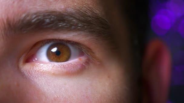 Nahaufnahme eines braunen Mannes mit weit aufgerissenem Auge, der aufgeregt in die Kamera auf dem Hintergrund blickt.