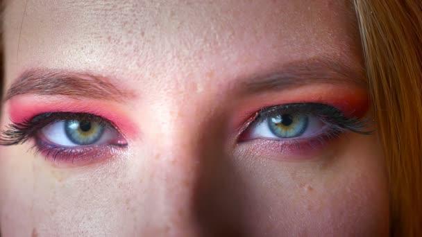 Detailní záběr na nádherné ženské modré oční make-up s odstíny růžové a zlaté úrovní očí. Oči, díval se zpříma na kameru s úsměvem výraz