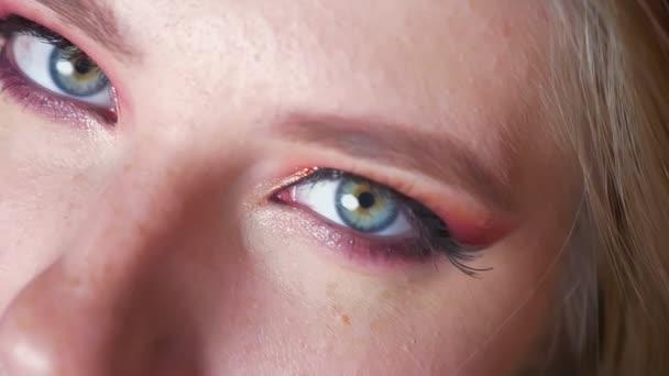 Detailní záběr na atraktivní ženské modré oči make-up s růžové stíny a golden úrovní očí při pohledu na fotoaparát
