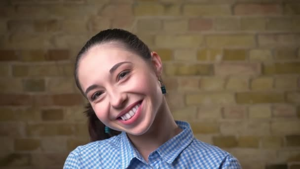 Close-up portrait of caucasian brunette woman with ponytail shyly watching with smile into camera on bricken wall background.