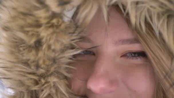 Close-up eye-portrait of beautiful young caucasian girl in fur hood flirtingly posing into camera on winter street background.