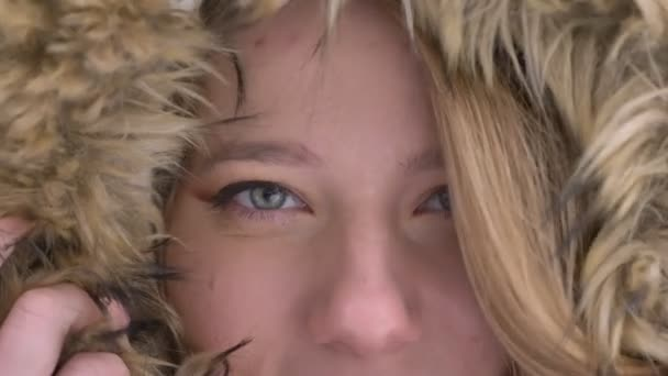 Close-up eye-portrait of beautiful young caucasian girl hiding in fur hood flirtingly posing into camera on winter street background.