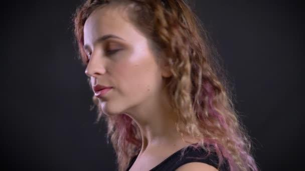 Nahaufnahme Porträt eines jungen Mädchens mit rosa Haaren wendet sich der Kamera zu und sieht gelassen auf schwarzem Hintergrund zu.