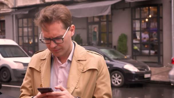 Detailní záběr na kavkazské muže v brýlích kontrola telefon stojící na ulici čeká na někoho dotyčného a frustrovaný ve městě