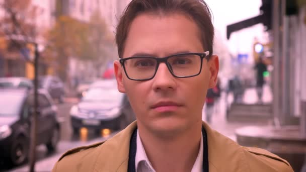 Closeup of adult caucasian man faced to camera looking forward in glasses standing on the street by the road and passing cars