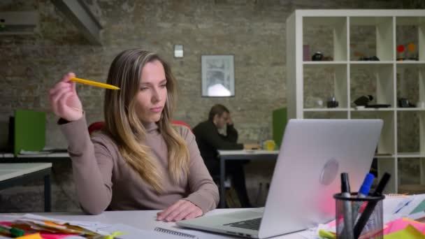 Nahaufnahme Porträt einer gelangweilten erwachsenen Büroangestellten, die abgelenkt ist und ihrem Job keine Aufmerksamkeit schenkt