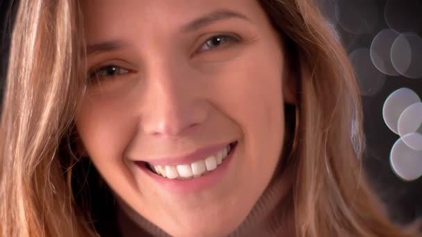 Vértes makró portréja boldog lenyűgöző kaukázusi női arc nézett egyenesen a kamera, és mosolyogva