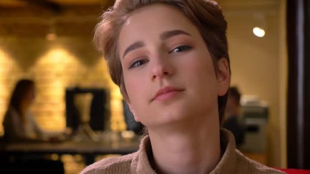 Detailní portrét mladé atraktivní krátké vlasy ženy dívat do kamery s klidným úsměvem v úřadu.