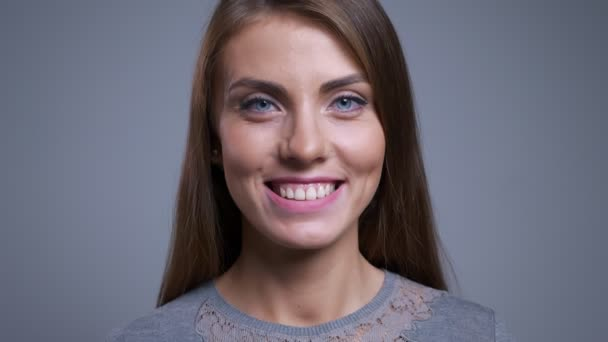 Closeup portrait of happy young caucasian woman smiling and looking straight at camera with background isolated on gray.