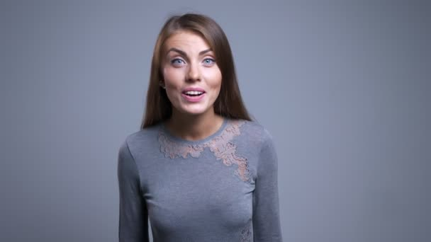Closeup portrait of attractive young caucasian female getting surprised looking at camera smiling and waving with her hand